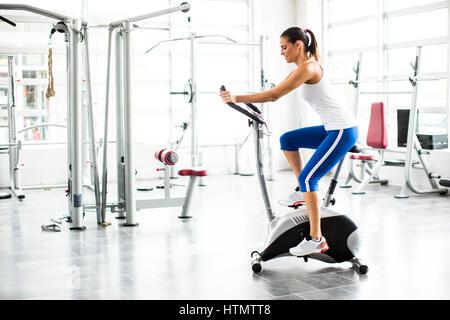 Aerobica spinning donna esercizio allenamento in palestra bici Foto Stock