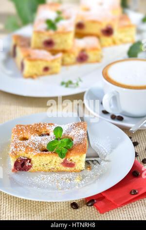 Delizioso pezzo di torta di ciliegie con un fresco bicchiere di cappuccino Foto Stock