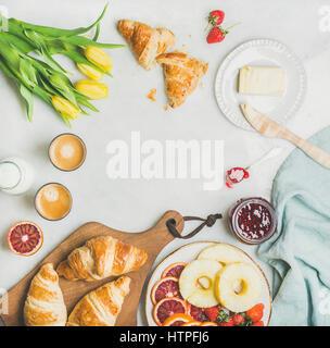 Tavolo per la colazione con cornetti, burro, marmellata di lamponi, frutta fresca, latte in bottiglia, caffè espresso Foto Stock