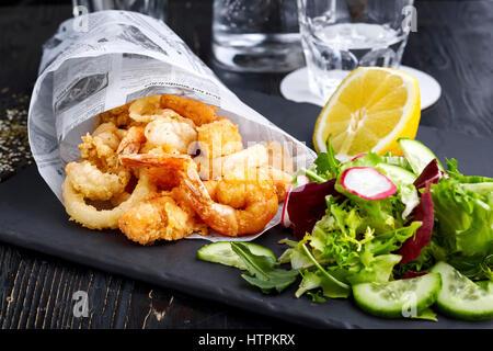Gamberi fritti nel cono di carta sulla piastra con insalata di verdure Foto Stock