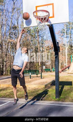 Montare giovane uomo muscolare il salto di gettare la pallacanestro in hoop