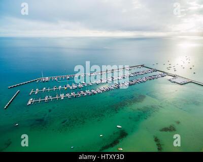 Antenna seascape di barche ormeggiate in marina e la bellissima baia di turchesi acque di sunrise Foto Stock