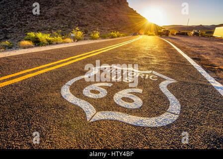 Strada segno sulla storica Route 66 nel deserto di Mojave fotografati contro il sole al tramonto Foto Stock