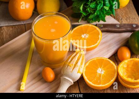 Agrumi Arance Limoni cumquat lime, menta fresca, alesatore appena premuto il succo in vetro su legno tavolo da cucina dalla finestra, vista dall'alto Foto Stock