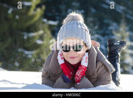 Donna felice avendo divertimento nella neve con laici lana rosso guanti e occhiali da sole mentre nevicava Foto Stock