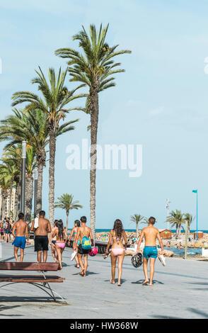 Alcuni giovani ragazze e ragazzi camminare a piedi nudi, wet costumi da bagno sul marciapiede dopo il nuoto nel Foto Stock
