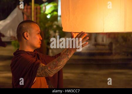 Monaco buddista detiene un tradizionale lanterna oscillante con una candela di notte.notte celebrazione in un tempio Foto Stock