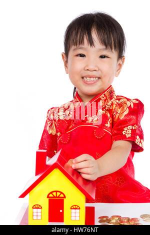 Il cinese Bambina mette le monete nel salvadanaio isloated su sfondo bianco Foto Stock