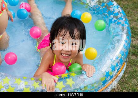 Asian poco ragazza cinese giocando in una gomma gonfiabile Piscina all'aperto Foto Stock