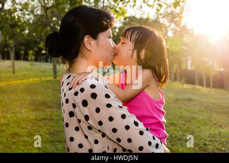 Cinese asiatici Bambine Kissing Madre al parco in serata. Foto Stock