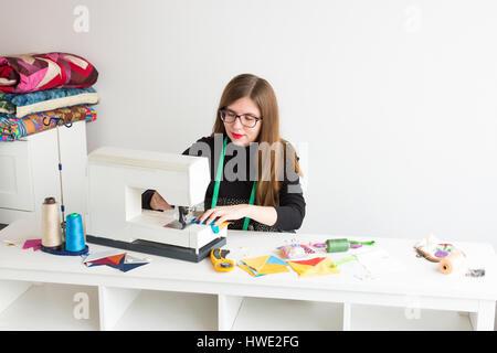 La bella sorridente ragazza giovane con occhiali sulla macchina da cucire il processo di creazione di mosaico. la Foto Stock
