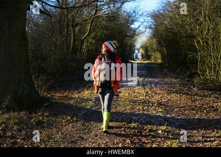 Donna che cammina lungo il percorso del paese portando i giovani nella baby sling Foto Stock