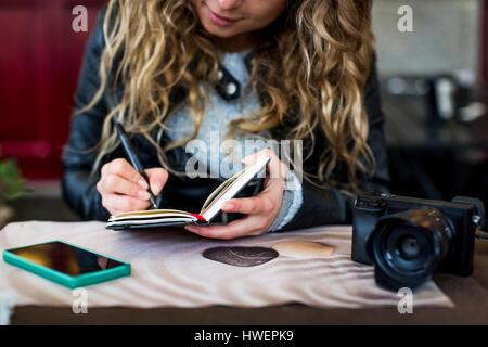 Donna al cafe iscritto nel notebook Foto Stock