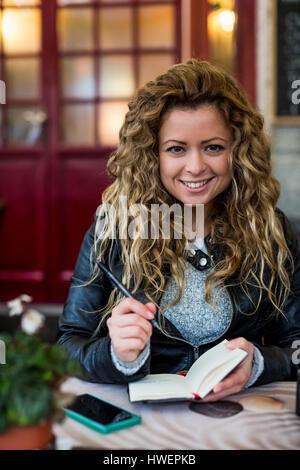 Donna al cafe iscritto nel notebook