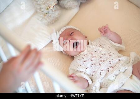 Carino neonato risiede nel presepe e guardando la madre Foto Stock