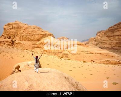 Bedouin in piedi su una roccia nel Wadi Rum desert in Giordania Foto Stock