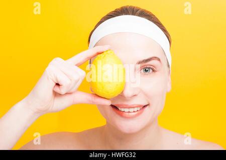 Bella femmina che copre il suo occhio con limone fresco come purezza e benessere concetto isolato su sfondo giallo Foto Stock