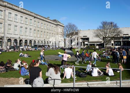 Gli studenti seduti intorno al sole sulla piazza di borsisti trinity college a Dublino Repubblica di Irlanda Foto Stock