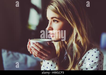 Ritratto di giovane bellissima femmina bere il tè e minuziosamente guardando fuori del coffee shop finestra mentre godendo il suo tempo libero da soli, nice busi