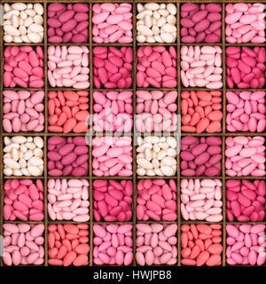 Un modello di perfetta di una piazza di legno scatola di archiviazione con nove scomparti, riempita con una selezione di confetti in sfumature di rosa. Queste amare s