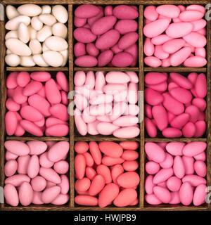 Piazza di legno scatola di archiviazione con nove scomparti, riempita con una selezione di confetti in sfumature di rosa. Queste bitter sweet tratta sono un tradit