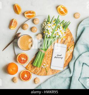 Caffè, biscotti, arance, fiori e telefono cellulare con buona mattina Foto Stock