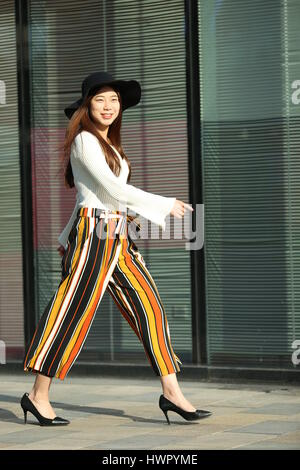 Beijin, Beijin, Cina. 23 Mar, 2017. Pechino, Cina-marzo 23 2017: (solo uso editoriale. Cina OUT) un pulcino ragazza cammina lungo la strada di Sanlitun, Pechino del fashion hub, marzo 23rd, 2017. Credito: SIPA Asia/ZUMA filo/Alamy Live News