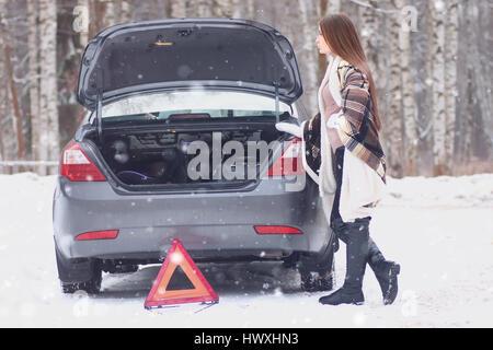 Ragazza avvolto in una coperta posto vicino alla vettura rotto Foto Stock