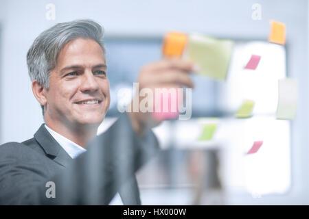 Imprenditore mettendo stricky note sulla lastra di vetro Foto Stock