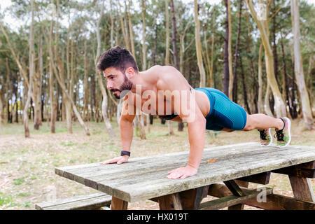 Uomo Barechested facendo push-up sul tavolo in legno all'esterno Foto Stock