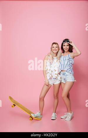 Felice di due giovani donne con lo skateboard in piedi e sorridente su sfondo rosa Foto Stock