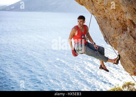 Maschio di rocciatore in appoggio mentre è appesa sulla fune prima del tentativo successivo sul percorso impegnativo Foto Stock