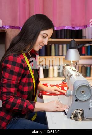 Ritratto di giovane donna seduta sarta e cuce sulla macchina da cucire. Sarta lavorare sulla macchina per cucire. Foto Stock