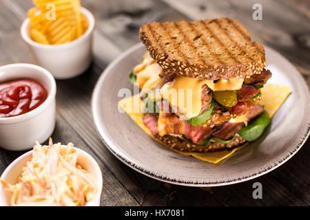 Grandi sandwich fatti in casa con un arrosto di manzo, pancetta, sottaceti, baby spinaci e Coleslaw medicazione in pane tostato Foto Stock