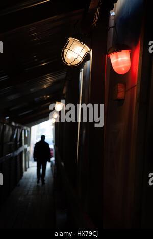 Uomo a camminare nella luce attraverso un tunnel scuro. In primo piano vi sono due di colore rosso e bianco lampade Foto Stock
