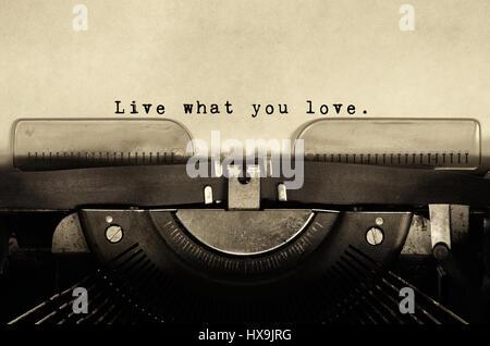 Vivere ciò che amate citazioni ispiratrici tipo sulla macchina da scrivere vintage. Foto Stock
