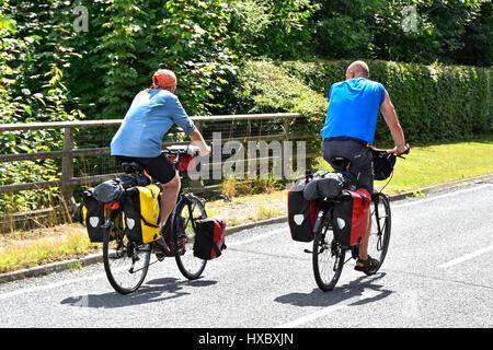 Paio di ciclismo su strada in inglese sul percorso ciclabile per bicicletta lungo il tranquillo paese lane in Essex Foto Stock