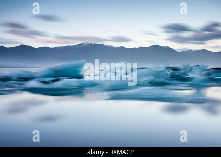Jokulsarlon laguna glaciale lunga esposizione al tramonto con gli iceberg in primo piano e le montagne sullo sfondo, Foto Stock