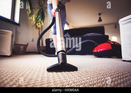 Donna Pulizia tappeto con un aspirapolvere in camera Foto Stock