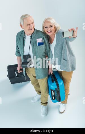 Felice coppia senior con borse da viaggio e dei passaporti rendendo selfie sullo smartphone, il concetto di viaggio Foto Stock
