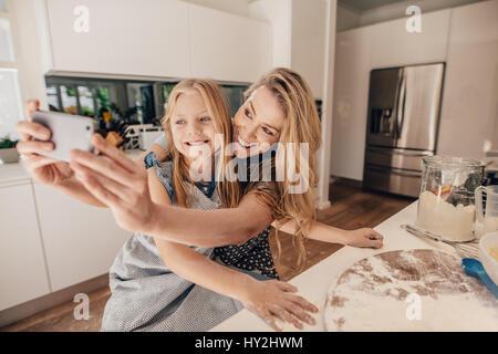 Carino bambina e la sua bella madre tenendo selfie sorridente e preparare l'impasto per la cottura in cucina. Felice Foto Stock