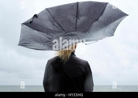 Polonia, niechorze, donna sotto l ombrello nero a guardare mar baltico Foto Stock