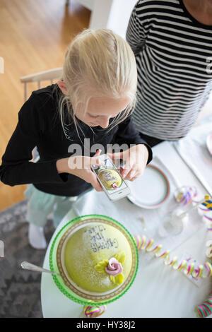 La Svezia, ragazza (12-13) fotografare la torta di compleanno con un telefono cellulare Foto Stock