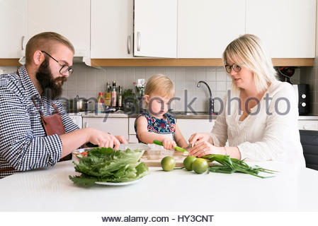 La Svezia, famiglia con un bambino (2-3) seduta a tavola Foto Stock