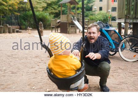 La Svezia, skane, Malmo, padre figlio oscillante ( 12-17 mesi) nel parco giochi Foto Stock