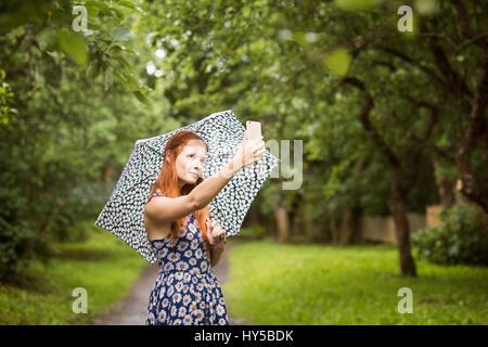 Finlandia, Pirkanmaa, tampere, donna che indossa abiti floreali in piedi con ombrello nel parco e tenendo selfie Foto Stock