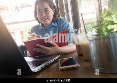 Giovani asiatici hipster donna iscritto su notebook mentre si lavora con il computer portatile in una caffetteria. Business Freelance starup nozione di attività