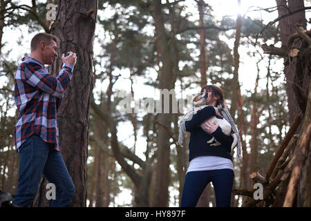 Un uomo prende una foto della sua compagna e il suo cane come si cammina nel bosco