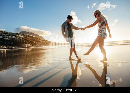 Bella coppia Giovane tenendo le mani e giocando sulla riva. Felice giovane coppia romantica in amore divertimento sulla spiaggia. Foto Stock