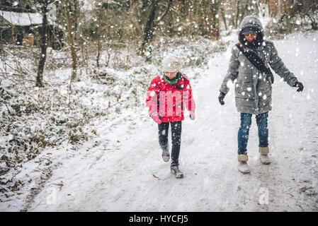 Madre e figlia escursionismo in bianco inverno forest Foto Stock